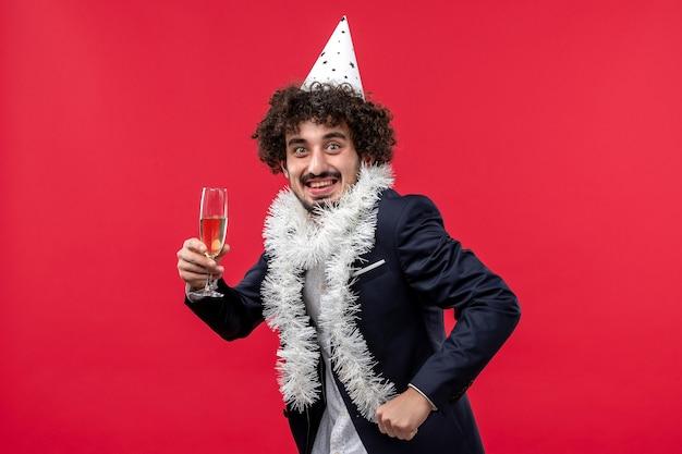 Вид спереди молодой самец празднует еще один год на красном полу, праздник человеческого рождества