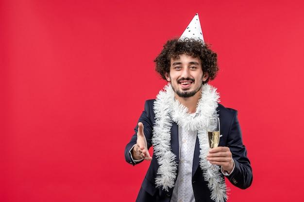 Вид спереди молодой самец празднует еще один год на красном полу праздника человеческая вечеринка