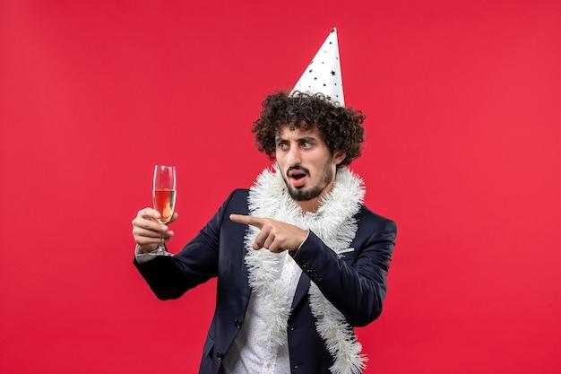 Вид спереди молодой мужчина празднует еще один год на красной стене, праздник человеческого рождества