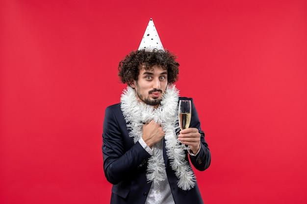 Вид спереди молодой мужчина празднует еще один год на вечеринке человеческих праздников на красной стене