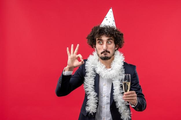 Вид спереди молодого мужчины, празднующего еще один год на красной стене
