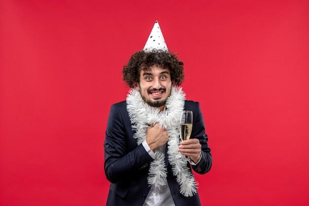 Giovane maschio di vista frontale che celebra un altro anno sulla festa di festa umana scrivania rossa