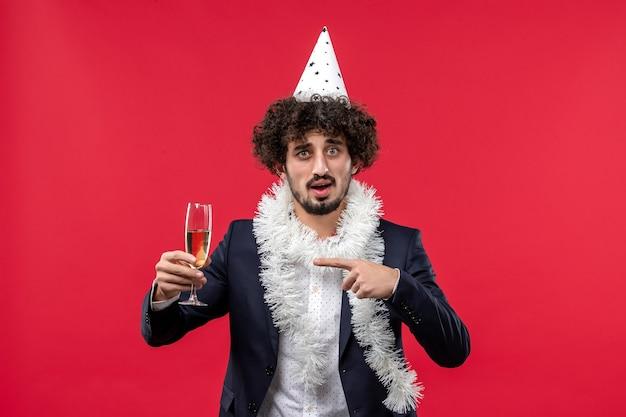 Вид спереди молодой мужчина празднует новый год на красной стене праздничной вечеринки рождества