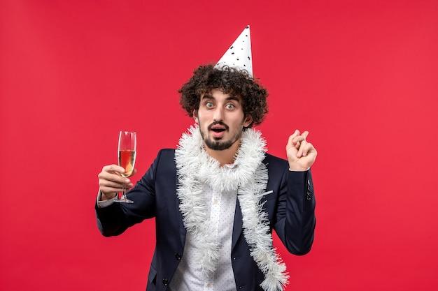 Вид спереди молодой самец празднует новый год на красной стене праздник человека рождество Бесплатные Фотографии