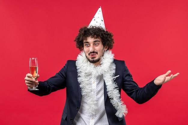 Giovane maschio di vista frontale che celebra il nuovo anno che viene sul natale rosso della festa di festa della parete