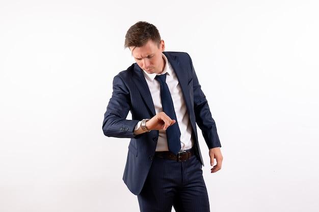 正面図若い男性は白い背景の上の古典的なスーツで時間をチェックします感情衣装ファッションモデル人間の男性