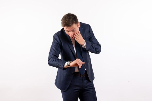 正面図若い男性は白い背景の感情の古典的なスーツで時間をチェックします人間の衣装ファッションモデル男性