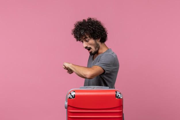 Vista frontale giovane maschio che controlla il tempo sullo spazio rosa pink