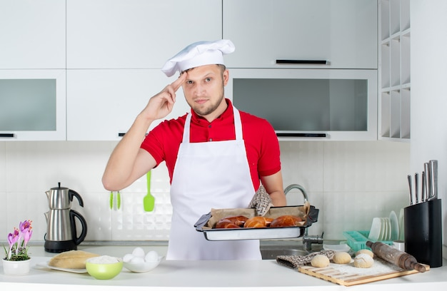 Front view of young male chef wearing holder holding freshly-baked pastries and feeling proud in the white kitchen