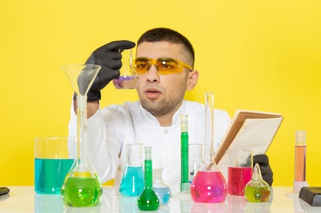 Вид спереди молодой мужчина-химик в белом костюме перед столом с цветными растворами, читающий блокнот на желтом столе, наука, работа, химия