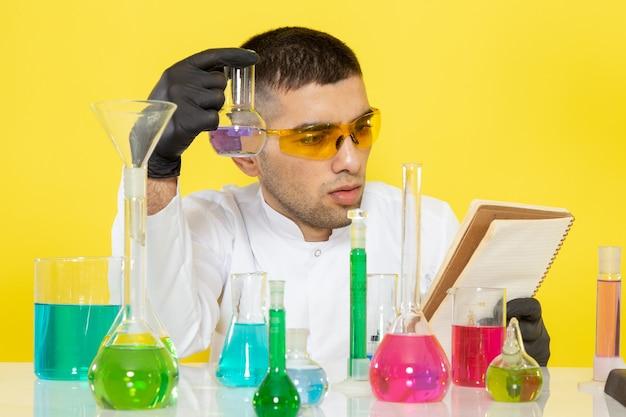 Вид спереди молодой химик в белом костюме перед столом с цветными растворами, читающий блокнот на желтом столе, научная работа, лаборатория химии