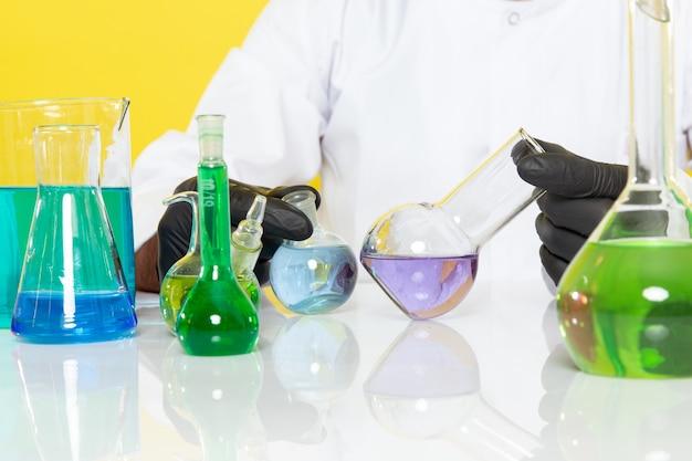 テーブルの前に白いスーツを着た若い男性の化学者の正面図黄色の壁の科学作業ラボの化学で彼らと一緒に働いている着色されたソリューション