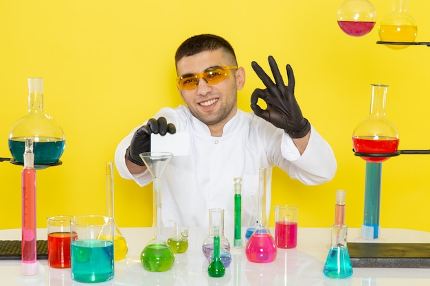 Front view young male chemist in white suit in front of table with colored solutions holding white card smiling on yellow wall science work lab chemistry