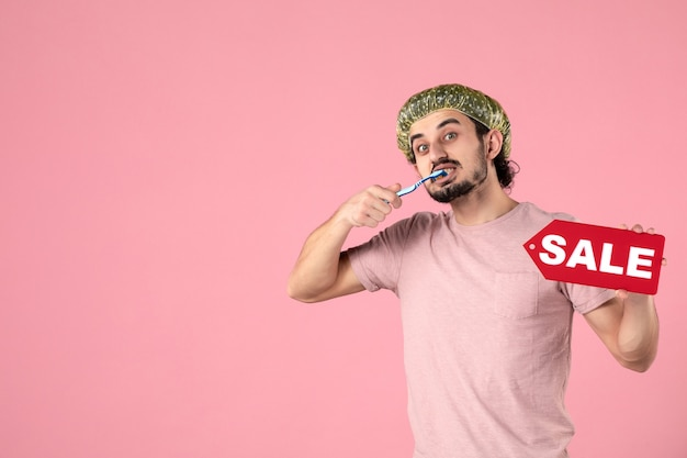 Vista frontale giovane maschio che pulisce i suoi denti e che tiene la targhetta di vendita su sfondo rosa