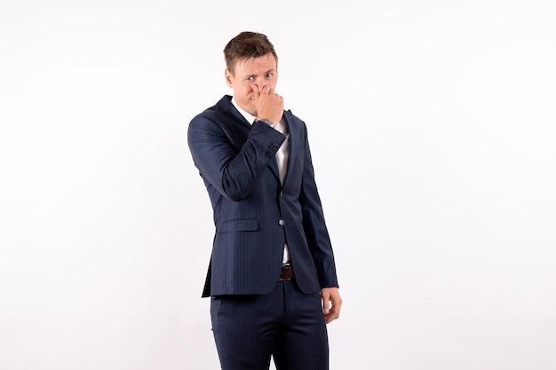 正面図白い背景の上の古典的なスーツで鼻を閉じる若い男性感情衣装ファッションモデル人間男性