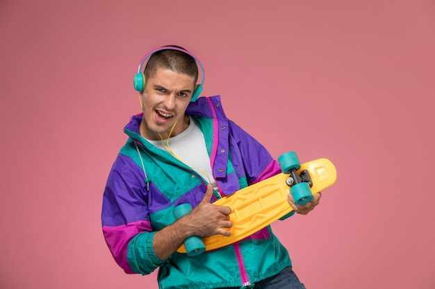 Front view young male in colorful coat listening to music and holding skateboard on the pink desk