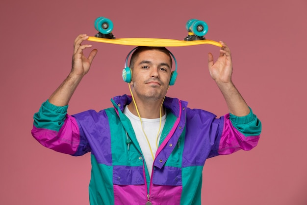Front view young male in colorful coat listening to music on the pink background