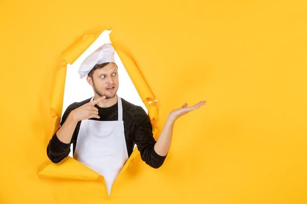 正面図若い男性料理人白いマントと黄色の背景の帽子で料理の仕事白人男性料理写真カラーキッチン