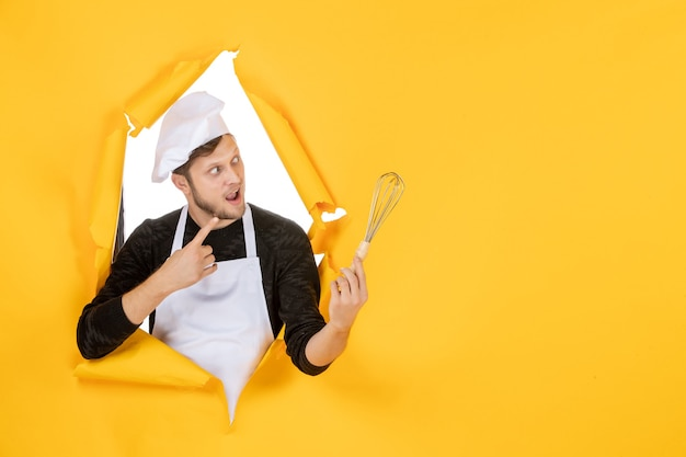 正面図黄色の背景に泡立て器を保持している白い岬の若い男性料理人料理料理キッチン仕事白い色の男