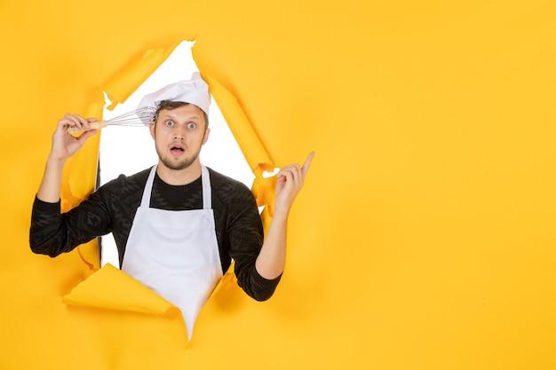 正面図黄色の背景に泡立て器を保持している白い岬の若い男性料理人写真食品料理キッチン白い色の男