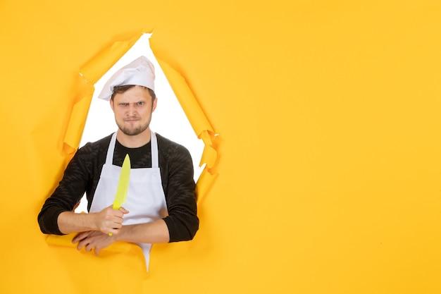 正面図黄色の背景に白いマントで若い男性料理人白い色のキッチン料理仕事人の写真