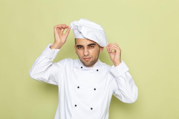 緑の白い帽子を修正する白いクックスーツで正面の若い男性クック