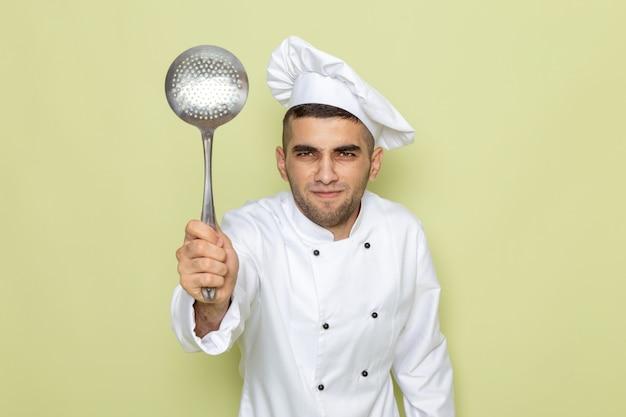 緑jに銀の食糧スプーンを保持している白いクックスーツで正面の若い男性クック