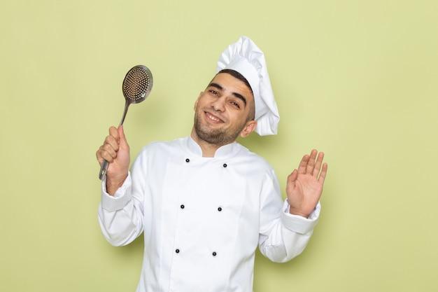 緑の笑顔で銀のスプーンを保持している白いクックスーツで正面の若い男性クック