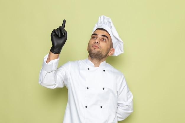 緑の革手袋でポーズをとって白いコックスーツで正面の若い男性クック