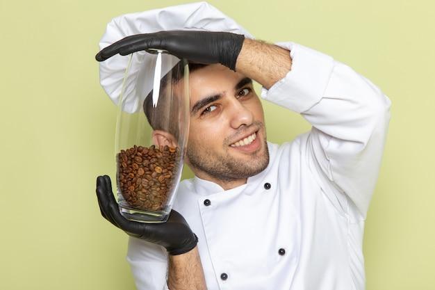 Вид спереди молодой мужчина-повар в белом костюме повара улыбается и держит семена кофе на зеленом