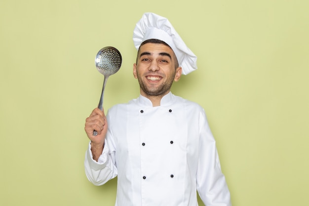 白いクックスーツ笑顔とグリーンのスプーンでポーズの若い男性クック正面