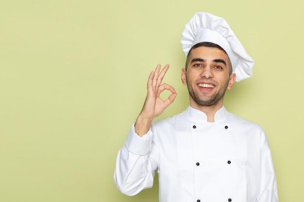 웃 고 녹색에 괜찮아 기호를 보여주는 흰색 쿡 정장에 전면보기 젊은 남성 요리사