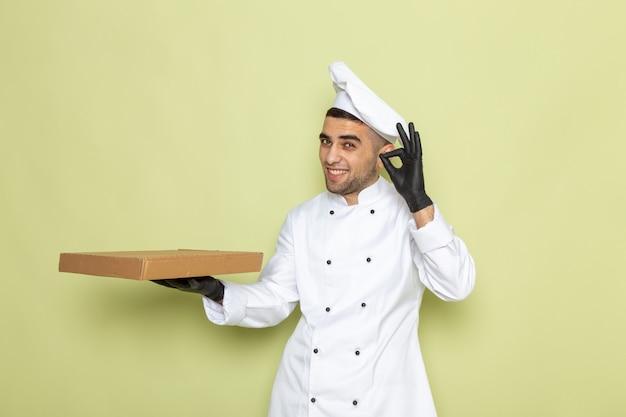 緑のボックスを保持している黒革の手袋を身に着けている白いクックスーツで正面の若い男性クック