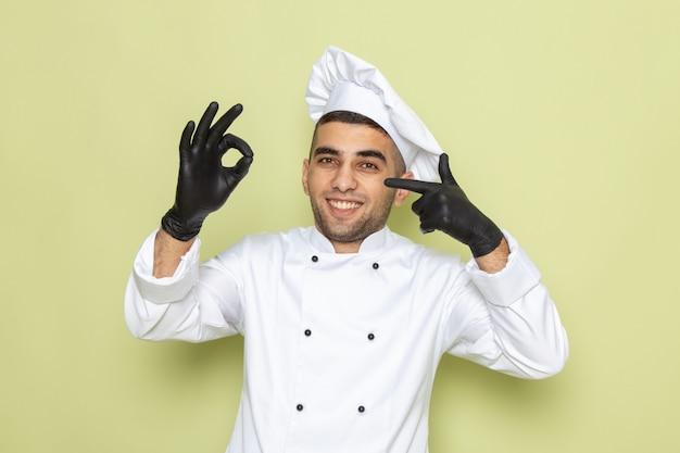 緑の笑顔で黒革の手袋を身に着けている白いクックスーツで正面の若い男性クック