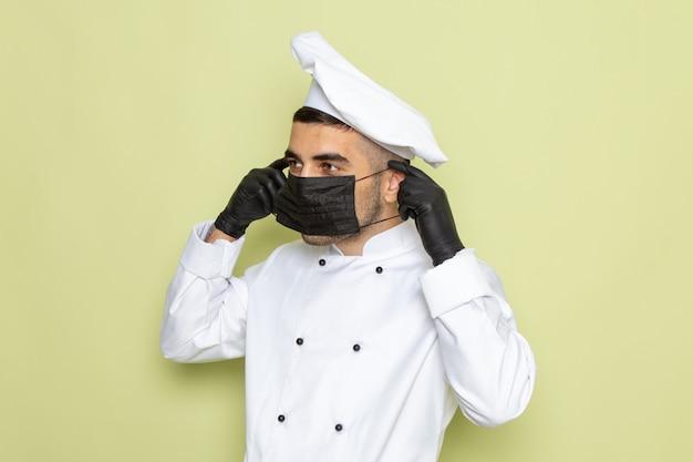 暗い手袋を着用し、緑の仕事料理制服男性にマスクを着ている白いクックスーツで正面の若い男性クック