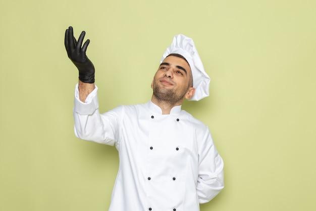 緑の空に探している黒い手袋と白いクックスーツで正面の若い男性クック