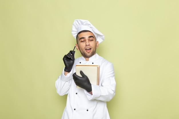 正面緑の手袋でメモを書く白いコックスーツで若い男性クック