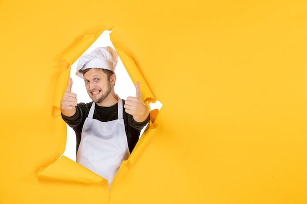 Front view young male cook in white cape and cap trying to smile on yellow background food job white man cuisine photo color kitchen