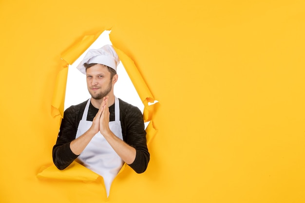 Front view young male cook in white cape and cap on yellow background food white man cuisine photo color kitchen job