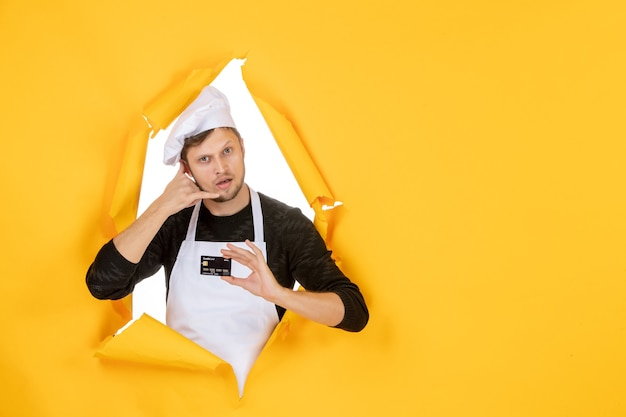Front view young male cook in white cape holding black bank card on the yellow background model white color cuisine job man food money