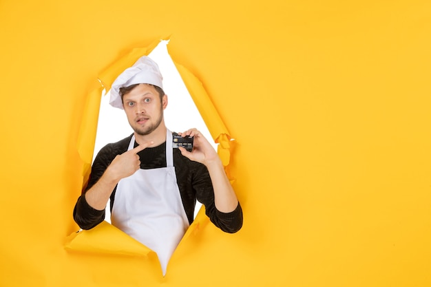 Front view young male cook in white cape holding black bank card on a yellow background white color cuisine job man food money