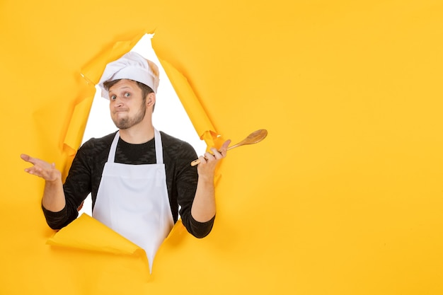 Vista frontale giovane cuoco maschio in mantello bianco che tiene cucchiaio di legno su sfondo giallo colore cucina foto cucina lavoro uomo bianco