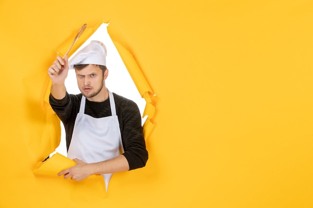 Front view young male cook in white cape holding wooden spoon on a yellow background white color kitchen cuisine job man food photo
