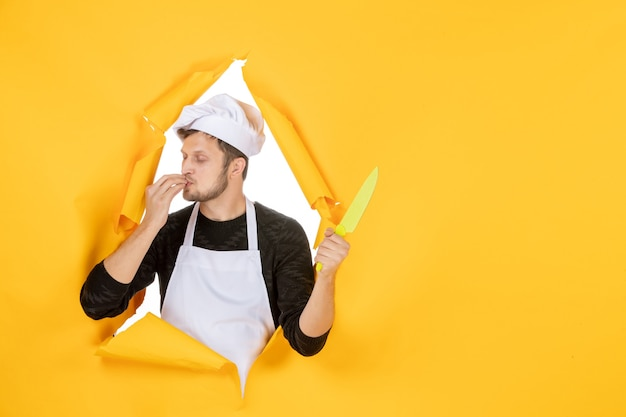 Front view young male cook in white cape on the yellow background white color cuisine job man food photo kitchen