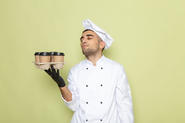 Front view young male cook in white cook suit holding several coffee cups on green