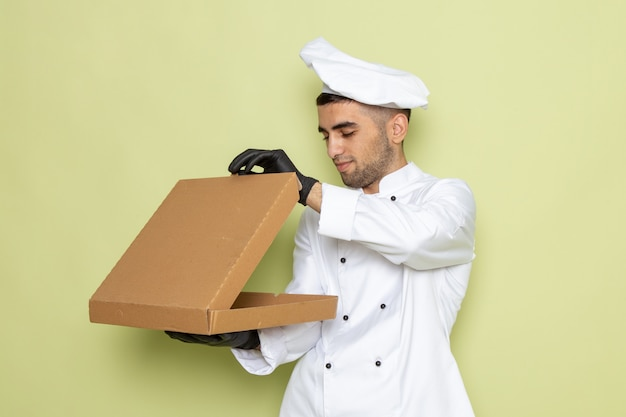 Front view young male cook in white cook suit wearing black leather gloves holding box opening it on green