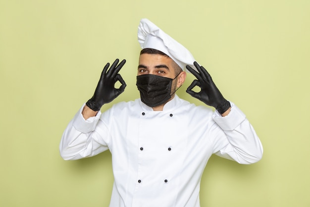 Front view young male cook in white cook suit wearing mask and gloves on green