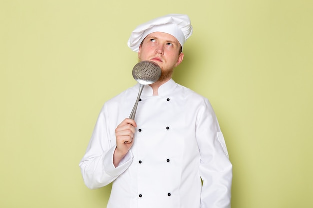 A front view young male cook in white cook suit white head cap holding big silver spoon thinking
