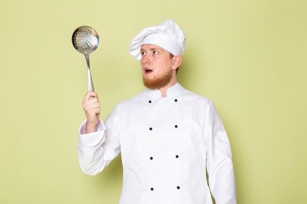 A front view young male cook in white cook suit white head cap holding big silver spoon