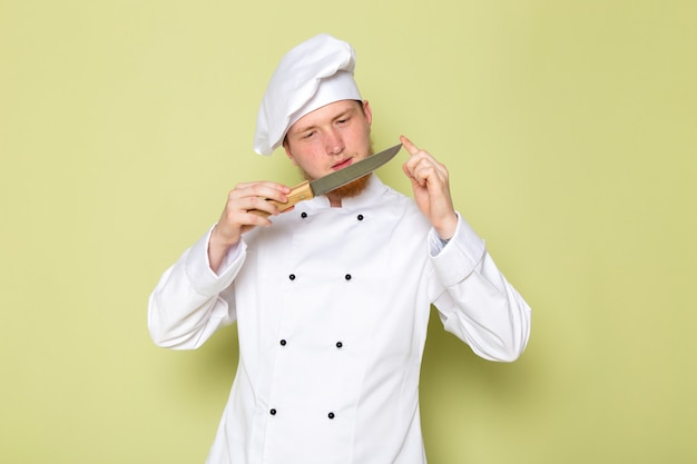 A front view young male cook in white cook suit white head cap holding checking knife